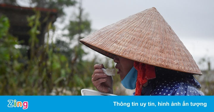 Người phụ nữ ăn cơm cứu trợ trong cơn mưa